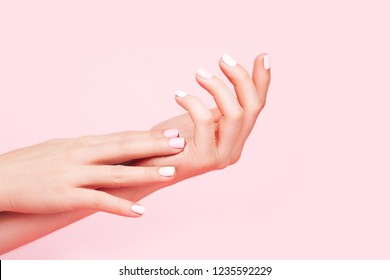 Tender hands with perfect pink manicure on trendy pastel pink background. Place for text.