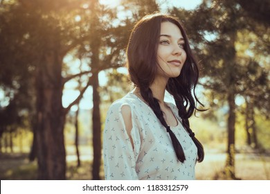 Tender happy woman in forest enjoying nature. Natural beauty girl outdoor in freedom enjoyment concept. Gorgeous mixed race Caucasian Asian girl posing on travel vacation holidays in dress. Close-up