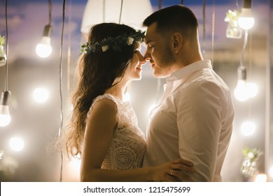 Tender hugs of young wedding couple standing before a wall with bright lamps