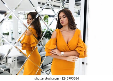 Tender lady in yellow dress with decollete standing in thestaurant near the mirror. Accessories on a hand, open shoulders and volume sleeves. Curly hairstyle and stylish makeup. Shooting indoor