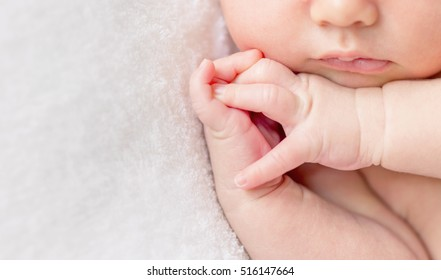 tender lips and nose and crossed fingers of a newborn baby asleep on a diaper, closeup