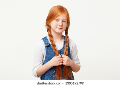 Tender little kind girl keeps in hands braided in two long plaits red hair, stands calmly directly looking camera, dressed in jeans overall dress over a white longsleeve isolated on white background