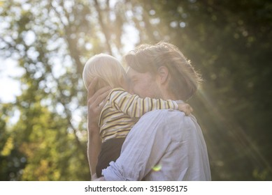 Tender loving moment between a young father and his toddler son - dad holding the boy in his arms hugging him happily in a beautiful nature with sunlight.