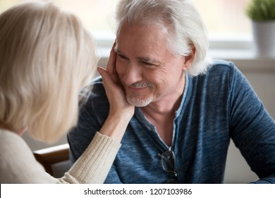 Tender loving senior wife caress beloved husband touching his face with hand, romantic aged couple enjoy sensual moment together, cuddling and looking in eyes, showing care. Elderly love concept