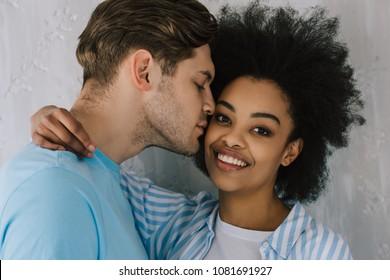 Tender man embracing and kissing african american girlfriend