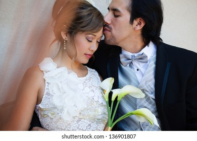 Tender moment between a beautiful Bride and Groom Mixed Ethnicity