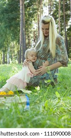 Tender moments of expectation: pregnant young mother with cute little daughter emracing her belly in a summer park