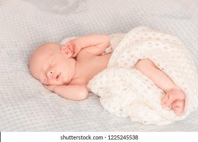 Tender newborn sleeping on belly on a blanket in cute props. Infant baby