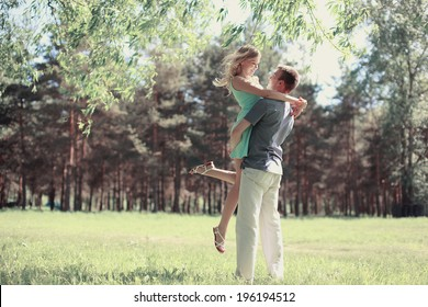 Tender photo lovely young happy couple in love, loving man holding on hands his woman carefree together outdoors walking at park