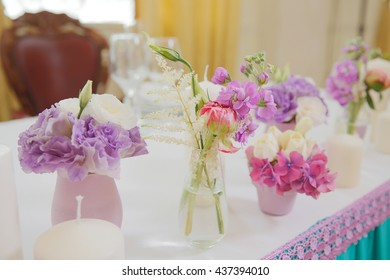 Tender pink and violet  flowers stand in small glass vases