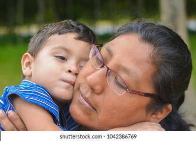 Tender portrait of latin mom with her little son outside.