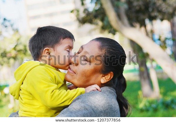 Tender portrait of little son kissing his mommy.