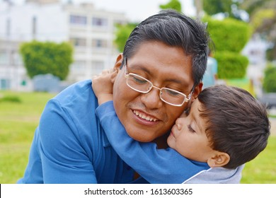 Tender portrait of native american man with his little son in the park.