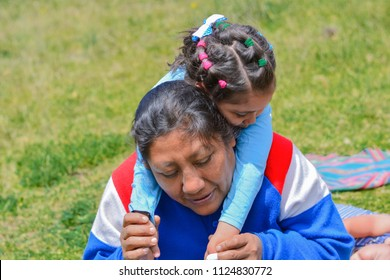 Tender portrait of native american woman with her little daughter in the countryside.