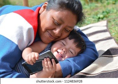 Tender portrait of native american woman with her little son in the countryside. The kid is holding the mobile phone.