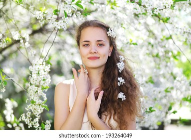 Tender portrait of a young cute girl in the garden, floral, spring concept