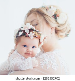 tender portrait of young mother holding infant baby girl, daughter. family look outfit