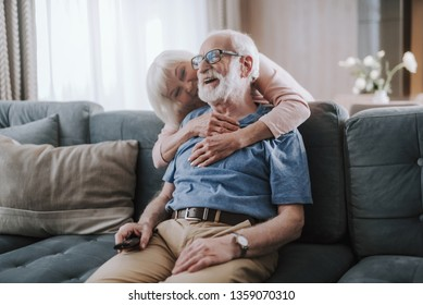 Tender relationship on retirement. Waist up portrait of cheerful aged man watching TV on sofa while his wife embracing him from back