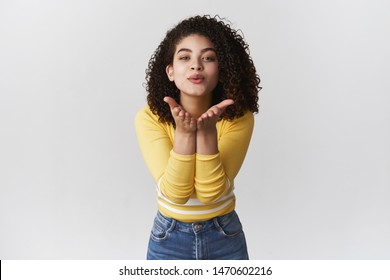 Tender romantic attractive feminine girlfriend curly-haired mixed-race lean camera hold hands near folded lips send air kiss blowing muah camera smiling flirty, standing white background cheeky