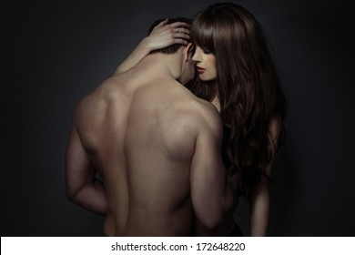 Tender romantic young lovers holding each other in a close intimate embrace , view from behind the bare back of the man
