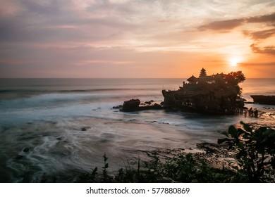 Tender sea sunset near famous tourist landmark of Bali island - Tanah Lot temple. Long exposure frozen water effect, Bali Indonesia. Tropical nature landscape of Indonesia, Bali. Tanah Lot temple Bali