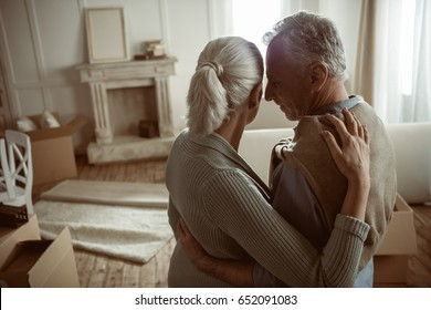 tender senior husband and wife embracing and looking at their home, moving out concept
