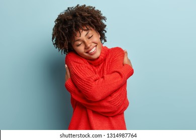 Tender sensual Afro American woman huggs herself, likes her new warm red cozy sweater, closes eyes with enjoy and pleasure, dreams about something pleasant, enjoys warm outfit during cold winter day