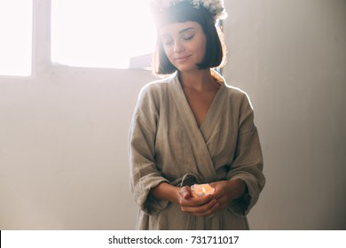 Tender and sensual photo of young natural beautiful woman in cotton linen organic bath robe holding melted wax candle, prepares for relaxation or spa at cosy home