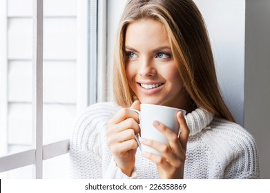 Tender softness. Beautiful young woman leaning the window at her apartment and holding a cup of coffee