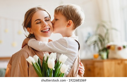 tender son kisses the happy mother and gives her a bouquet of tulips, congratulating her on mother's day during holiday celebration at home - Shutterstock ID 1922681069