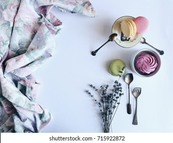 Tender vintage stylish macarons set, with lavender, fabrics, porcelain rabbit and sweet blueberry marshmallow. Top view, vintage silver spoons. White background.