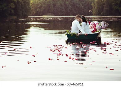 Tender wedding couple is sitting in boat with flowers