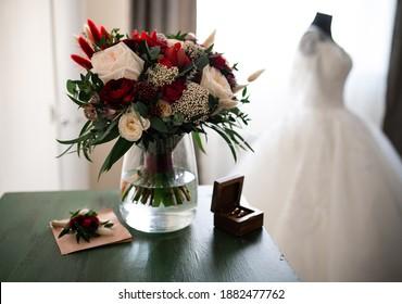 Tender weddingday. Wedding bouquet and blurred wedding dress near the window