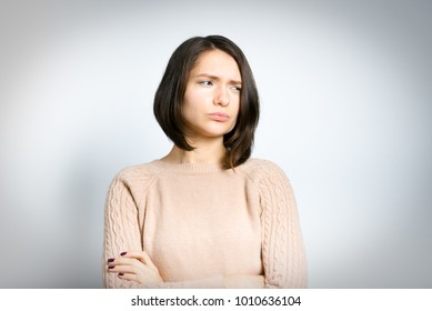 tender woman is offended, in a pink sweater, isolated against a background, studio photo