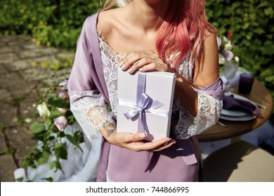 Tender woman with pink hair poses in violet robe with white present box