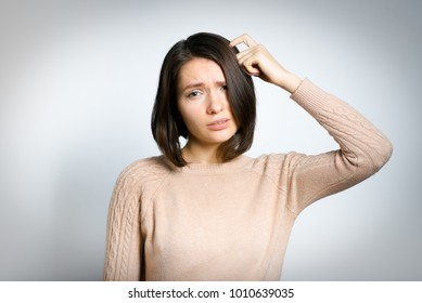 tender woman remembers something, in a pink sweater, isolated against a background, studio photo