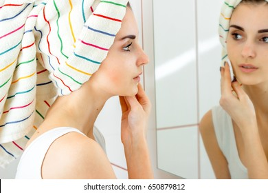 tender young girl with towel on the hair looks in the mirror and rubs your face with a cotton disk