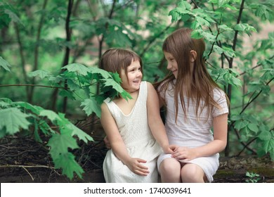 Tender young girls children sit on logs near a maple tree. Children talk and sincerely communicate, intimacy and openness, trust between sisters. Sibling and childhood relationship concept