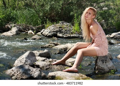 Tender young woman swimming in the pond among water lilies basking in the sun in shallow waters