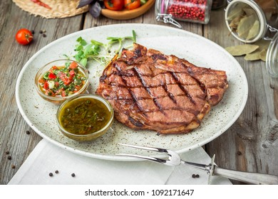Tenderloin steak on plate with sauce, on a wooden table