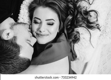 Tenderly kissing couple. Man and woman lying towards down. Kiss on the cheek