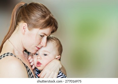 Tenderness. Beautiful mother is hugging her cute fair hair son. Image with toning and blur background