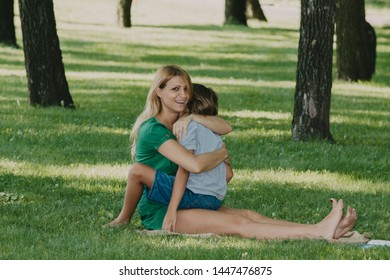 tenderness of a beautiful mother. Beautiful mother with slender legs punishes her son on a green lawn between trees