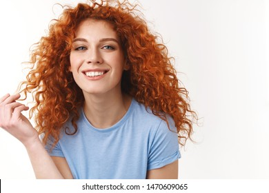 Tenderness, beauty, haircare concept. Alluring sensual young woman with natural curly red hair, rolling strand on finger silly, smiling toothy looking happy and coquettish, standing white background