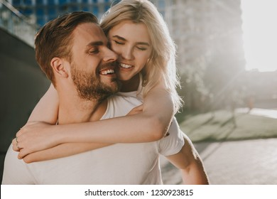 Tenderness in every move. Happy young couple brightly smiling with closed eyes. He carefully holding her on his back. Copy space on right side