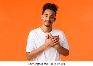 Tenderness, relationship and care concept. Romantic handsome young african-american male with moustache, press hands to heart and smiling toughed, feeling grateful or delighted, orange background