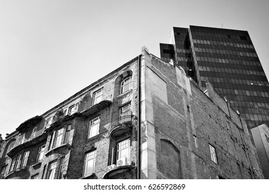 Tenement house on the background of a modern office building.Black and white