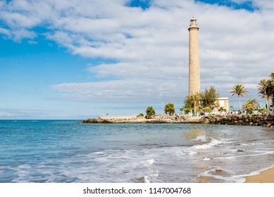 Tenerife, Canarias islands/ Spain - July 22, 2018: Empty beach of tourists and high lighthouse on Canarias, view of bay with palms. Blue Atlantic ocean and beach on Gran Canaria.