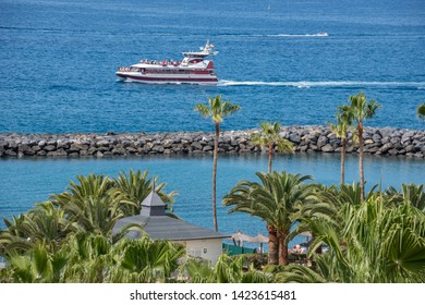 Tenerife, Canary islands - april 22, 2019: Tour boat for tourists sailing in front of an area of gardens on the coast of Adeje, south of the island