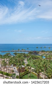 Tenerife, Canary islands - april 22, 2019: Scene with a helicopter flying over an area of gardens on the coast of Adeje, south of the island